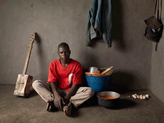 Bovenste foto: Mahamudi Charles zit in de derde klas van de basisschool (2005). Inmiddels is hij 25 (foto onder) en noemen zijn dorpsgenoten hem 'Banjo Man.' Foto's: Jan Banning