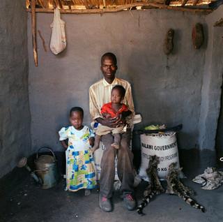 Saulos Fanuel (25) met dochter Ketelina (2) en zoon Lefiyamu (1). Hij is de zoon van het dorpshoofd. Naast hem een zak kunstmest en twee kattenhuiden. Dickisoni, 2005.