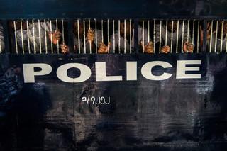 Omgeven door stofwolken rijden twee betraliede politiebusjes de oprijlaan van de rechtbank op. Binnen wordt luid gezongen, buiten zingt een groep meerennende mensen luidkeels mee. Foto: Andreas Stahl
