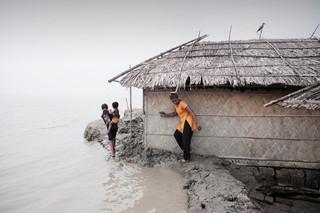 De land onder dit huis aan de kust van Bangladesh wordt bijna door de zee ingenomen. Foto: Alessandro Grassani / Hollandse Hoogte