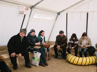 Wachtenden die de grens tussen door Oekraïne en DNR gecontroleerd gebied willen oversteken. Ze bivakkeren in een Artsen zonder Grenzen-tent die in de bufferzone staat, soms duurt het uren voor de grens overgestoken kan worden. Maart, 2016. Foto: Christopher Nunn