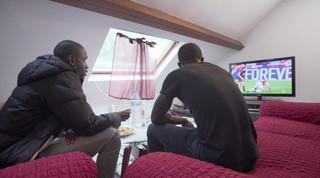 Op de zolderkamer van Laye (rechts) wordt er voetbal gekeken met Abou (links). Beeld: Bas Rozenbeek
