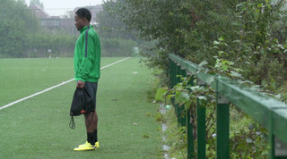 Een speler die al een club gevonden heeft, kijkt naar de spelers van La Roue in de regen. Beeld: Bas Rozenbeek