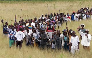 Zimbabwanen die zich klaarmaken om bezet land te bebouwen, zwaaien met landbouwwerktuigen in Harare op 13 april 2000. Foto: Reuters