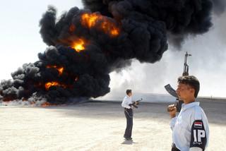 Gewapende Iraakse politiemannen staan voor een brandende tankwagen op 20 september 2003 in Fallujah, zo'n vijftig kilometer buiten Bagdad. Foto: Ramzi Haidar / AFP