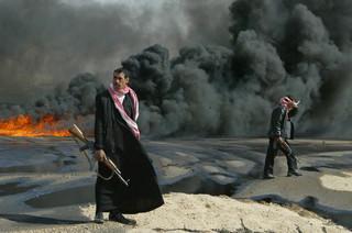 Een Iraakse politieman houdt de wacht bij een oliepijpleiding bij de stad Kerbala, zo'n 110 kilometer buiten Bagdad op 23 februari 2004. Foto: Faleh Kheiber / Reuters