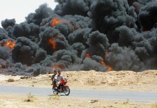 Twee Irakezen rijden op hun brommer langs een donkere rookwolk bij een oliepijpleiding dicht bij Barwanah, Irak, op 25 juni 2003. Foto: Marwan Naamani / AFP