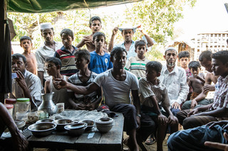 Our interview with a resident of Dar Paing. Others throng around him and repeatedly interrupt the conversation. Photo by Andreas Staahl