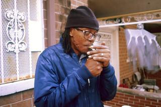 Anthony steekt een sigaret op voor het huis van zijn schoonmoeder. Foto: Horatio Baltz (voor De Correspondent)