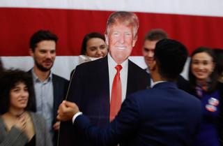 Een man draagt een uit karton gesneden Donald Trump tijdens een evenement op de Amerikaanse ambassade in Macedonië op de verkiezingsdag. Foto: Boris Grdanoski / AP