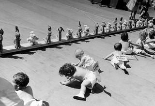 Kruipwedstrijd waar baby's naar een rij knuffels moeten kruipen. Foto: Cornell Capa / Getty Images