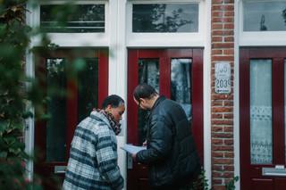 Twee medewerken van Doras (een organisatie voor maatschappelijke dienstverlening in Amsterdam-Noord) gaan de deuren af van mensen met schulden. Uit de serie 'Schuldig.' Foto: Jean Counet