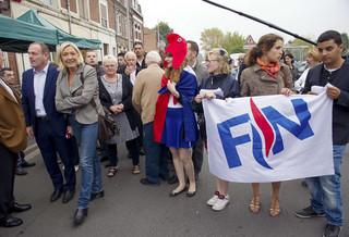 Steeve Briois (helemaal links), burgemeester van Hénin-Beaumont, en Marine le Pen komen aan bij de vlooienmarkt op 14 september 2014. Foto: Philippe Huguen / AFP