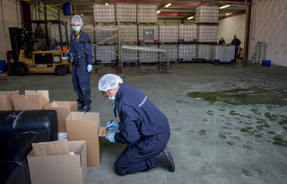 Politieagenten doen onderzoek in een groot drugslaboratorium in het Brabantse dorp Hoogerheide. Het vermoeden bestaat dat in het laboratorium grondstof voor synthetische drugs werd gemaakt. Foto: Marco de Swart / ANP