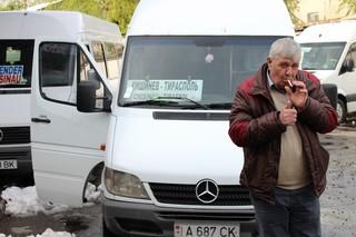 Een man steekt een sigaret op bij een taxibus van de Moldavische hoofdstad Chisinau naar de Transnistrische hoofdstad Tiraspol. Het nummerbord heeft de Transnistrische vlag.