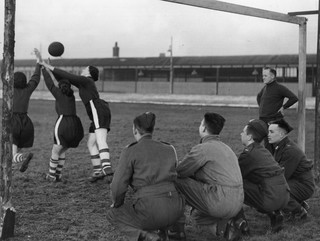Soldaten kijken toe bij een training van een pas gevormd vrouwen voetbalelftal bij 'the Bolton Women's Football And Athletic Club', 1939. Foto: Fox Photos / Getty