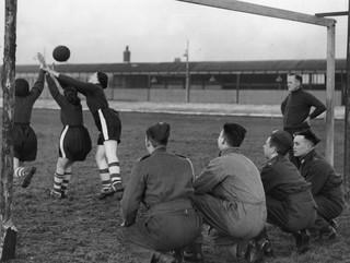Soldaten kijken toe bij een training van een pas gevormd vrouwen voetbalelftal bij 'the Bolton Women's Football And Athletic Club', 1939. Foto: Fox Photos / Getty