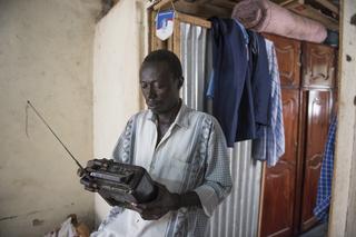 Thomas Ali luistert naar de radio om op de hoogte te blijven van het internationale nieuws. Juba, Zuid-Soedan. Foto: Charles Lomodong (voor De Correspondent)