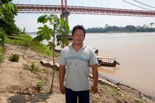 Arnaldo Sanchez langs de oever van de Madre de Dios. Op de achtergrond: de nieuwe brug van de Interoceanic Highway. Foto: Rochi León (voor De Correspondent)