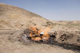 Brandend aardgas uit een scheur in de grond. Uit de serie 'Oil City' door Eugenio Grosso