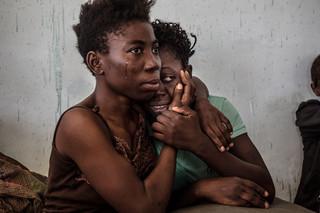Nigeriaanse migranten zoeken steun bij elkaar in het detentiecentrum voor vluchtelingen en migranten in Surman, Libië, op 17 Augustus 2016. In dit centrum zitten honderden vrouwen vast onder hachelijke omstandigheden. Velen vertellen regelmatig te worden geslagen, seksueel te worden misbruikt en niet voldoende eten en drinken te krijgen. Foto:  Daniel Etter / Redux