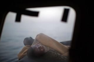 Migranten slapen op het dek van de Golfo Azzurro terwijl dit reddingsschip de haven van Pozallo binnenvaart. Er zijn honderden migranten aan boord die zijn gered door leden van Open Arms op 17 juni, 2017. Foto: Emilio Morenatti / AP