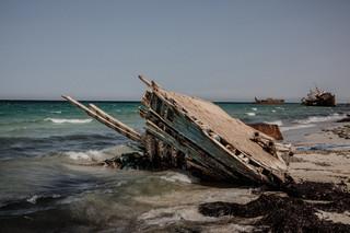 De overblijfselen van een vluchtelingenboot liggen op het strand van Zuwara op 17 augustus 2016, Libië. Zuwara was een van de belangrijkste vertrekpunten voor vluchtelingen die naar Europa werden gesmokkeld, maar omdat de gemeenteraad mensensmokkel in 2015 verbood is Zuwara overgegaan op diesel- en oliesmokkel. De mensensmokkel heeft zich verplaatst naar de dichtbijgelegen plaats Sabartah. Foto: Daniel Etter / Redux