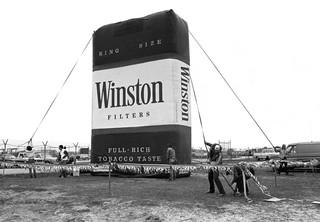 Werklui zetten een opblaasbaar Winston-sigarettenpak op voorafgaand aan de Daytona 500 in Florida, 1980. R.J. Reynolds Tobacco Company was in de jaren 80, voordat sigarettenreclame in Amerika werd verboden, de grootste sponsor van NASCAR. Foto: Robert Alexander / Archive Photos / Getty Images