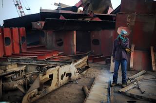 Een Pakistaanse lasser neemt een pauze van het snijden van metalen constructies, Pakistan, 2012. Foto: Roberto Schmidt / AFP