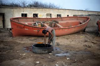 Een werknemer haalt water uit een put om zichzelf te wassen na een dag hard werken op een sloopwerf, Pakistan, 2012. Foto: Roberto Schmidt / AFP
