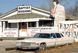 Een replica van een Cadillac die Elvis reed voor de deur bij het Elvis Is Alive Museum in 2007. Foto: AP / Kyle Ericson