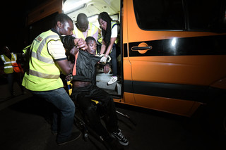 Een gewonde terugkeerder wordt een ambulance in geholpen na aankomst in Nigeria, 5 december 2017. Foto: Pius Utomi