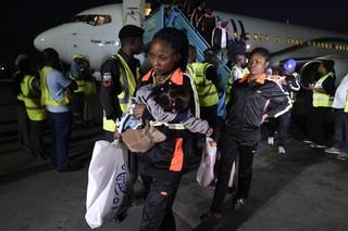 Een moeder verlaat een gecharterd vliegtuig dat 150 migranten uit Libië terugbracht op de internationale luchthaven Murtala Mohammed in Lagos, 5 december 2017. Foto: Pius Utomi