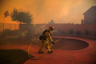 De brandweer probeert een huis te redden in Lake Elsinore, Californië, 9 augustus 2018. Foto: David Mcnew / ANP