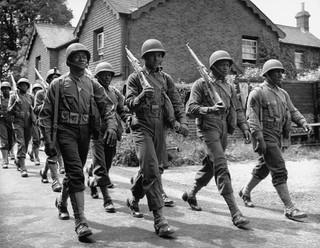 De eerste Afro-Amerikaanse troepen die de Verenigde Staten ooit naar Engeland stuurde, marcheren terug naar de militaire basis. Foto uit 1942 van David E. Sherman / Getty.