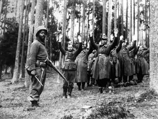 Een Afro-Amerikaanse soldaat houdt de wacht bij een groep gevangen nazi's in een Duits bos, april 1945. Foto: Interim Archives / Getty.