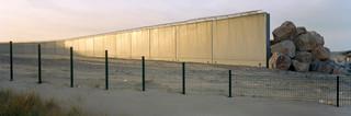 Een recent gebouwde muur rondom de haven van Calais, Noord-Frankrijk. De muur zou migranten die proberen naar het Verenigd Koninkrijk te gaan, moeten tegenhouden. Foto: Kai Wiedenhöfer, februari 2018