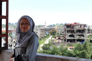 Saawiya Ibrahim Amate, met erachter wat rest van haar geboortestad Marawi. Foto: Moh Saaduddin, 24 september 2018. Onder het artikel kun je meer lezen over de maker van deze foto.
