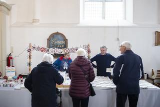 Bezoekers staan voor een kraampje tijdens de jaarlijkse kerstmarkt in Dreischor, 8 december 2018. Foto: Peter de Krom (voor De Correspondent)