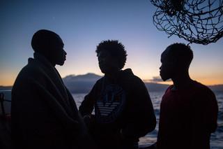 Drie migranten in gesprek op het dek van de Sea-Watch 3, nabij de Siciliaanse kust, 8 juni 2018. Foto: Erik Marquardt