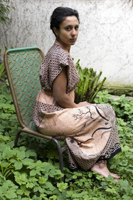 Charisma Pical in een jurk van oma en planten in de Hortus Botanicus. Foto: Amber Toorop (voor De Correspondent)