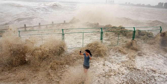 Een Chinese journalist raakt doorweekt terwijl ze probeert te berichten over het natuurfenomeen van de Qianjing golf in Haining (in de oost-Chinese provincie Zhejiang). Foto: Hollandse Hoogte