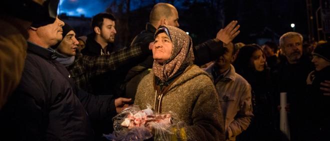 Een oude vrouw toont slachtafval om haar onvrede en honger te verbeelden tijdens protesten in Sarajevo op 8 februari 2014. Foto: Jodi Hilton