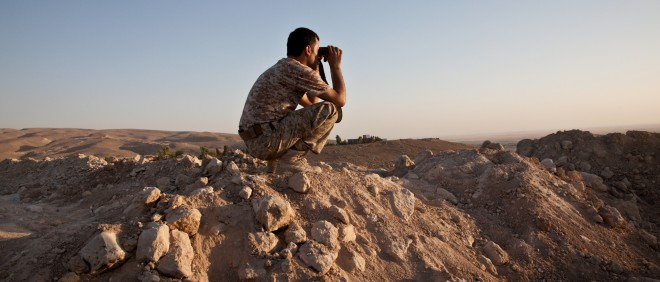 12 augustus 2014: Een Koerdische strijder kijkt uit over de stad Makhmour in Irak, die ze kort daarvoor hebben heroverd op IS. Foto: Sebastian Meyer/Hollandse Hoogte