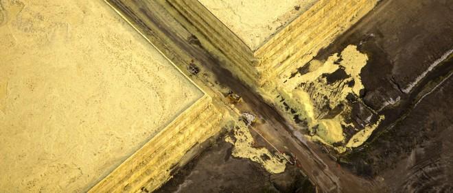 Uit ruwe bitumen moet zwavel worden onttrokken, dat vervolgens in bergen wordt opgeslagen. Dit is onderdeel van de open mijn bij Fort McMurray in Canada. Foto: Hollandse Hoogte