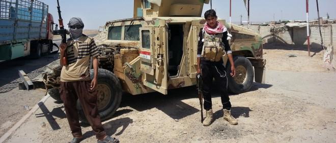 19 juni 2014: Twee IS strijders voor een ingerekende Iraakse legertruck bij een checkpoint aan de rand van de olieraffinaderij van Baiji, zo'n 250 kilometer ten noorden van de Iraakse hoofdstad Bagdad. Foto: Hollandse Hoogte
