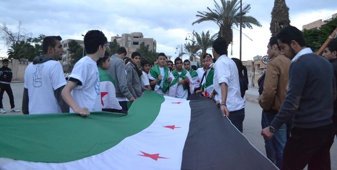 22 april 2012: Haqquna-leden dragen de Syrische onafhankelijkheidsvlag door de straten van Raqqa in een demonstratie tegen een bloedbad nabij Damascus. Foto: Ghaith aal Fakhri