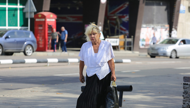 Een vrouw loopt aan de overkant van muziekbar en hotel Liverpool in de Oost-Oekraïense stad Donetsk. Foto: Aleksej Filippov (voor De Correspondent)