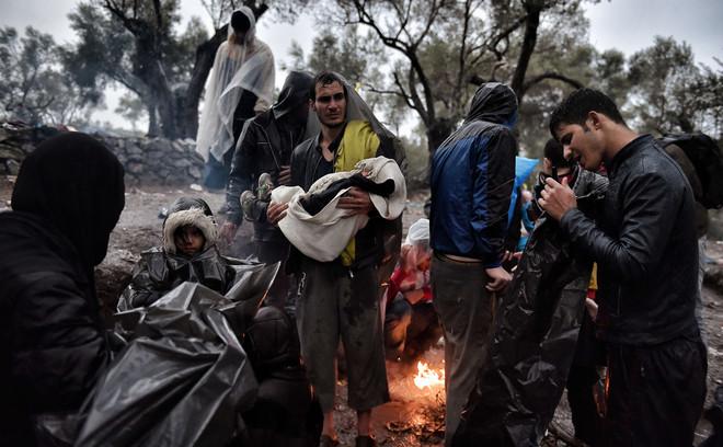 Syrische vluchtelingen wachten tot ze worden toegelaten in het vluchtelingenkamp op het Griekse eiland Lesbos. De families moeten vaak kilometers lopen en lang wachten voor ze worden geregistreerd en toegelaten in de opvangkampen. Foto: Aris Messinis/AFP