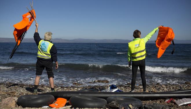 Lesbos, Griekenland (2 nov 2015). Vrijwilligers seinen vluchtelingen richting land. Foto: Hollandse Hoogte